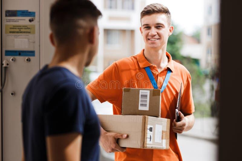 佩带橙色T恤杉和名牌的一个微笑的人交付小包到客户 友好的工作者,高 库存照片