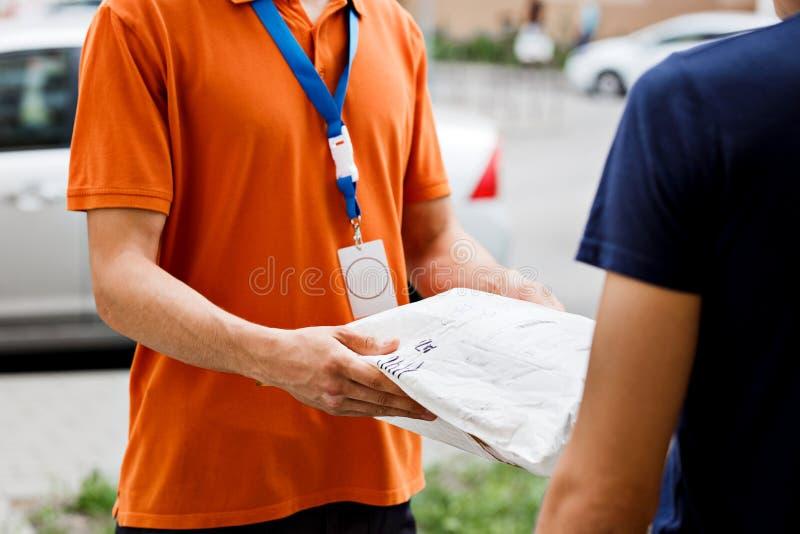 佩带橙色T恤杉和名牌的人交付一个小包到客户 友好的工作者,优质 免版税库存照片