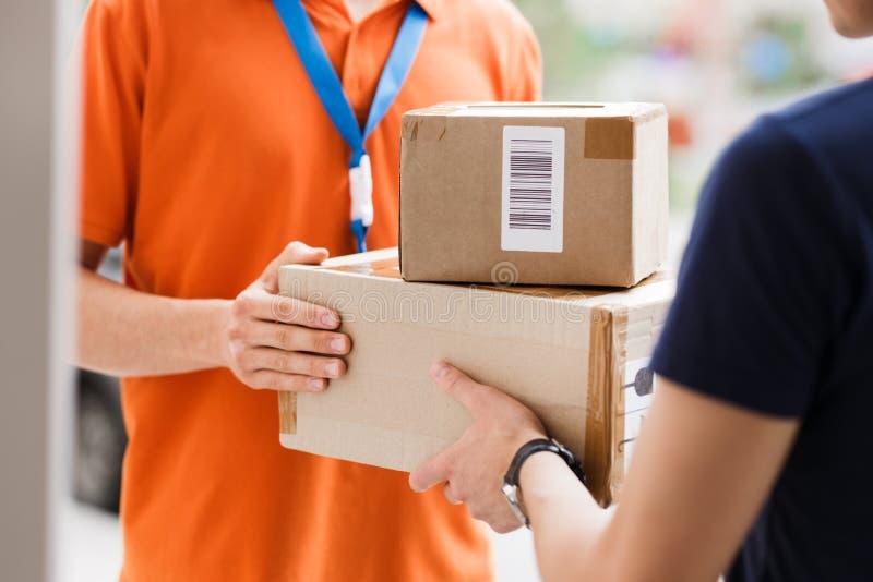 佩带橙色T恤杉和名牌的人交付小包到客户 友好的工作者,优质 免版税库存图片