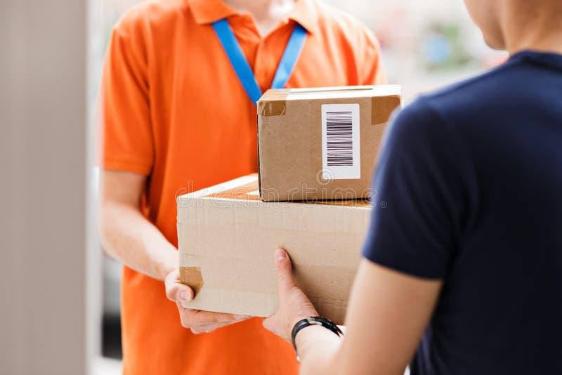 佩带橙色T恤杉和名牌的人交付小包到客户 友好的工作者,优质 库存照片