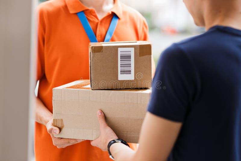 佩带橙色T恤杉和名牌的人交付小包到客户 友好的工作者,优质 库存图片