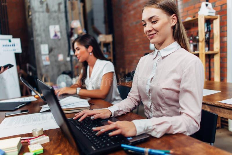 佩带正式工作服的友好的女性办公室工作者键入在运转在创造性的机构中的膝上型计算机键盘 免版税图库摄影