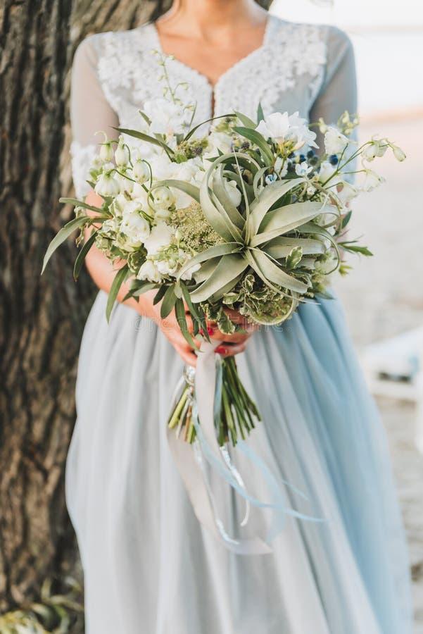 佩带浅兰的婚纱藏品花束的新娘 免版税库存图片