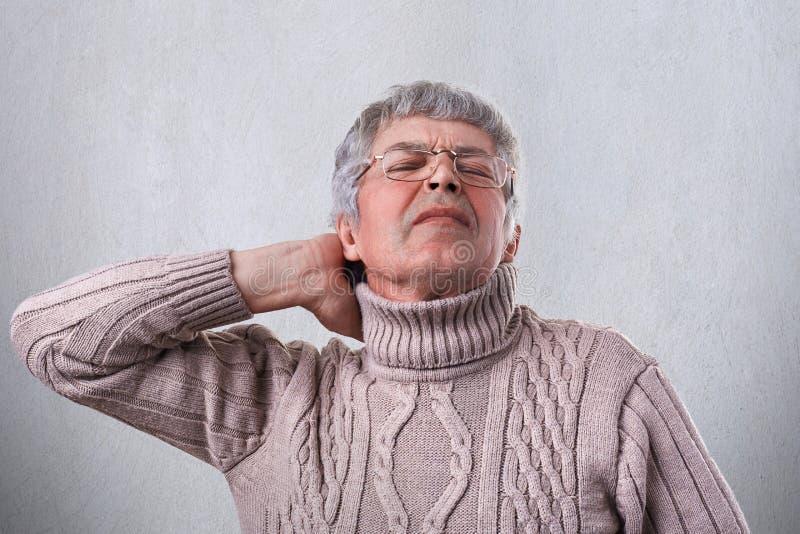 佩带温暖的毛线衣和镜片的一个成熟人握他的在是的脖子的手疲乏在工作以后在庭院里 疲乏成熟 免版税图库摄影