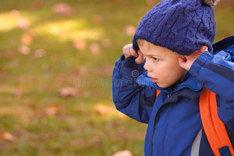 佩带温暖的蓝色帽子和蓝色的小白肤金发的男孩 免版税库存照片
