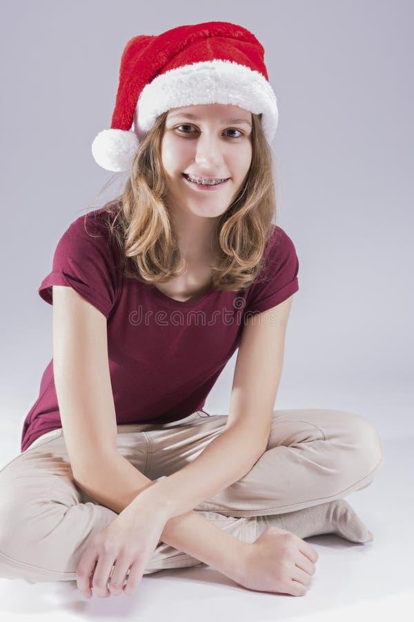 佩带牙齿牙托架的圣诞老人帽子的愉快和微笑的十几岁的女孩 库存图片