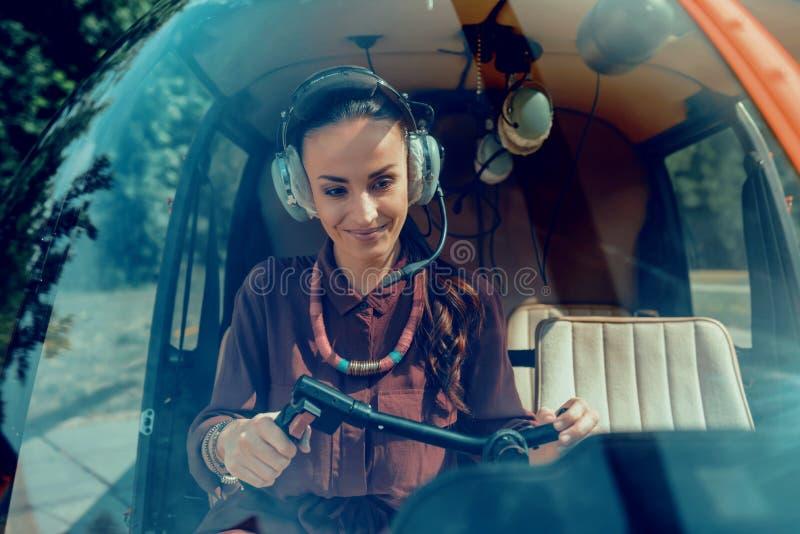 佩带特别耳机的快乐的吸引人的妇女,当是直升机飞行员时 库存照片