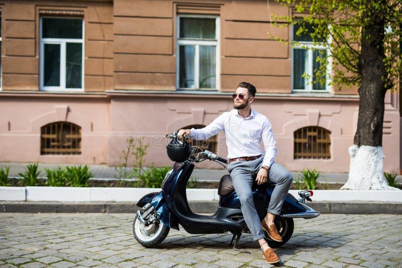 佩带现代太阳镜和一正式衣服坐的等待在城市街道上的一辆摩托车的时髦的时髦人 图库摄影