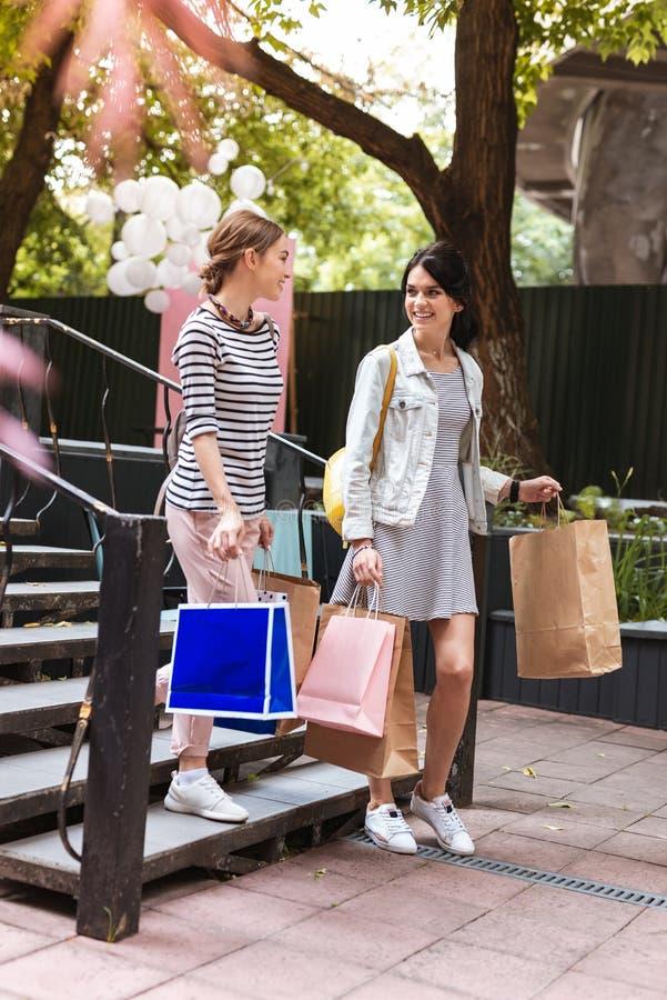 佩带白色运动鞋的两个时髦的朋友去咖啡馆在购物以后 库存照片