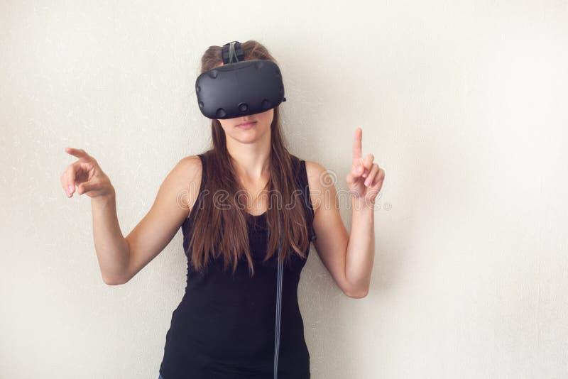 佩带真正耳机的年轻英俊的妇女 使用VR玻璃的激动的行家 空的演播室墙壁背景 图库摄影