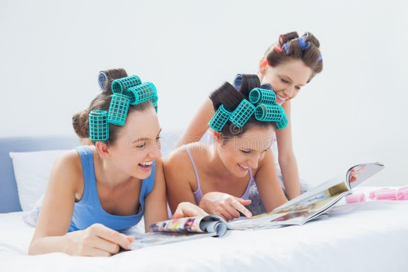 佩带睡衣和头发路辗的女孩坐在与magaz的床上 库存照片