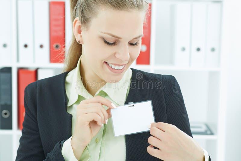 佩带空白的徽章的年轻微笑的女商人 在胸口人身分标签的名牌 名片大模型 免版税库存照片
