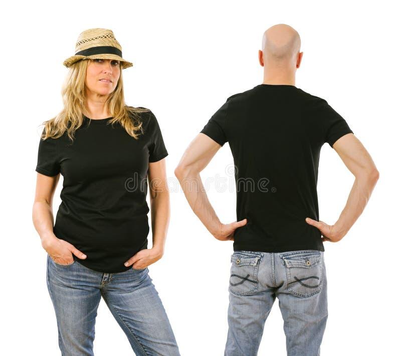 佩带空白的黑衬衫的硬前胸和后面的妇女和人 图库摄影