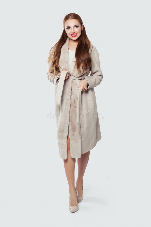 佩带米黄外套和高跟鞋的美丽的式样妇女站立反对白色墙壁背景 免版税图库摄影