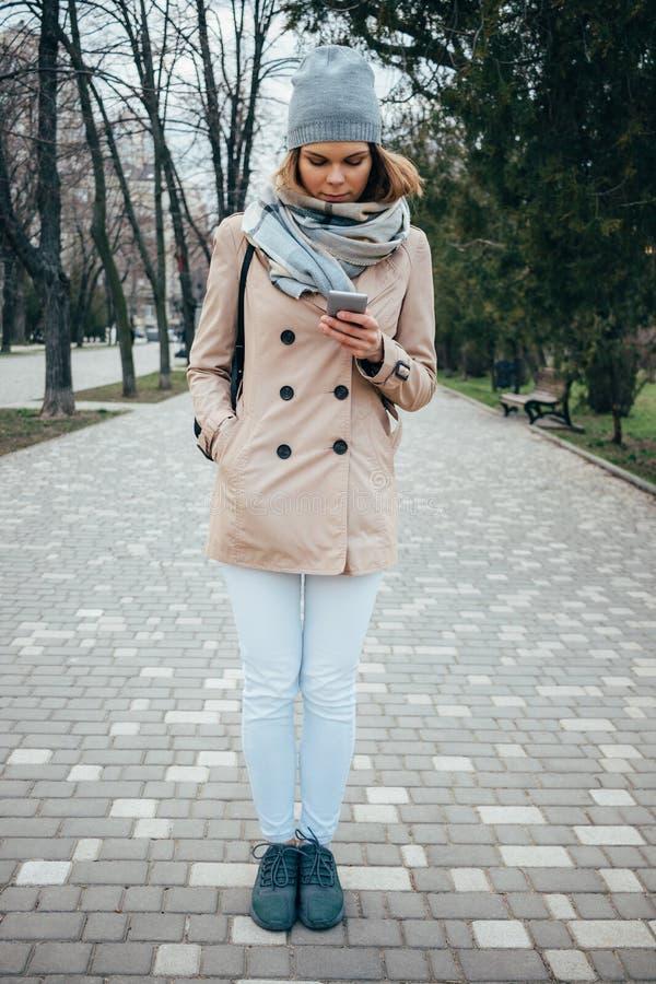 佩带米黄trenc的年轻女人全长垂直的画象 图库摄影