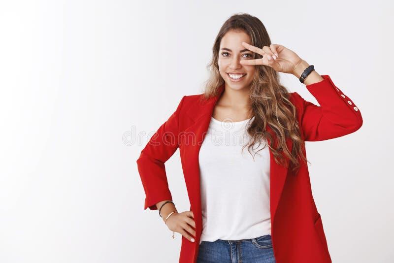 佩带红色夹克感觉乐观显示的胜利和平姿态眼睛的幸运逗人喜爱的被加强的正面女孩,微笑 免版税库存照片