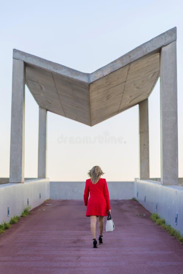 佩带红色夹克白色提包wh的一名白肤金发的妇女的后方图象 库存照片
