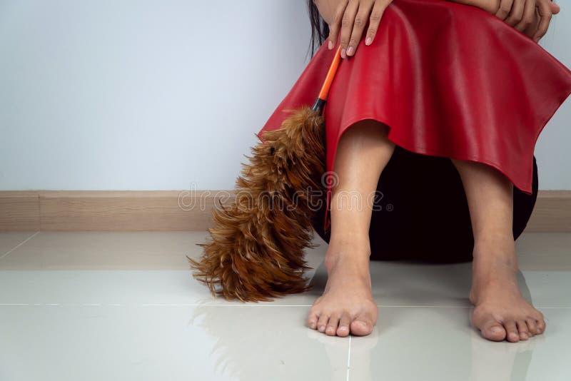 佩带红色布料的中年主妇坐地板 她的感觉乏味和疲乏对必须清洗房子 库存图片
