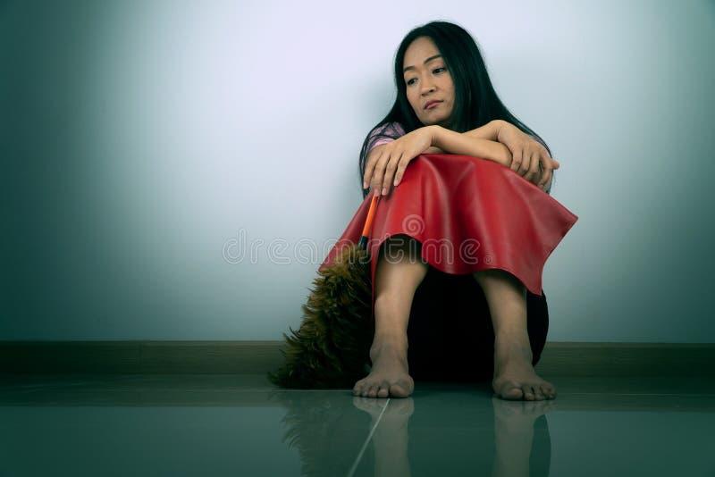 佩带红色布料的中年主妇坐地板 她的感觉乏味和疲乏对必须清洗房子 免版税库存图片