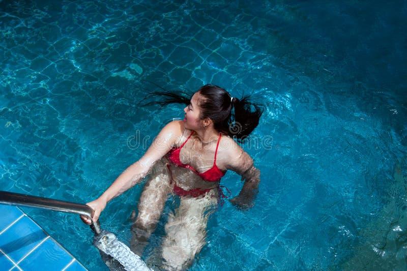 佩带红色比基尼泳装游泳和站立在台阶的俏丽的亚裔妇女在游泳场 图库摄影
