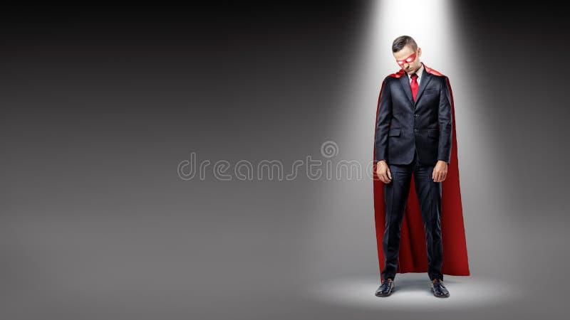 佩带红色超人海角的一个哀伤的商人站立在与他的肩膀的聚光灯下降了 免版税库存图片