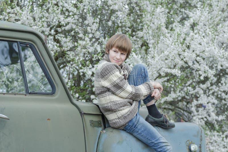 佩带羊毛制手工编织的鹿的休息的少年 图库摄影