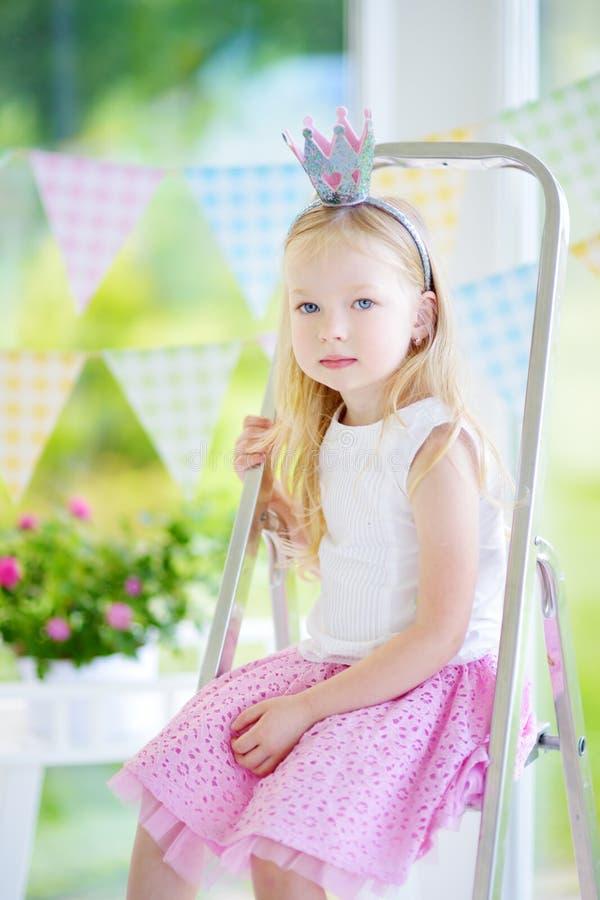 佩带美丽的礼服和公主冠状头饰的逗人喜爱的小女孩画象  免版税库存图片