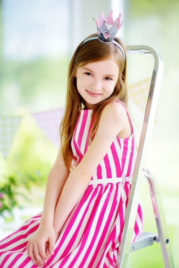 佩带美丽的礼服和公主冠状头饰的逗人喜爱的小女孩画象  免版税库存照片