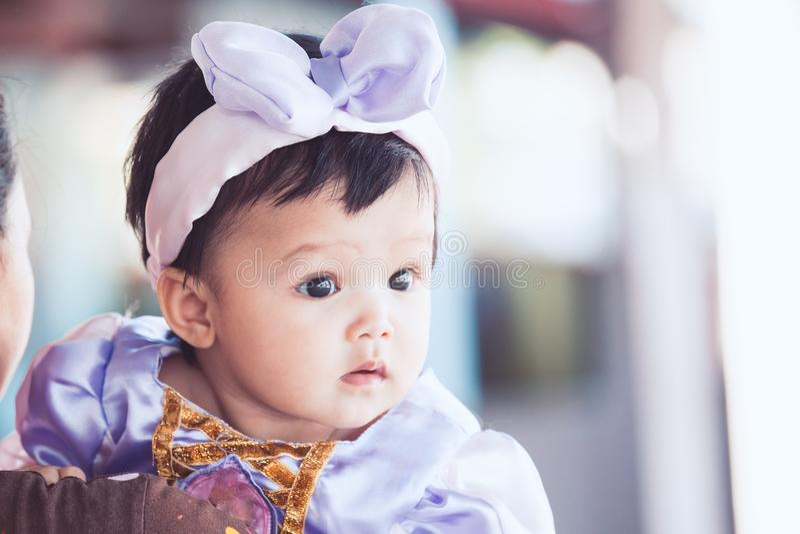 佩带美好的弓的逗人喜爱的亚裔女婴画象  免版税库存照片