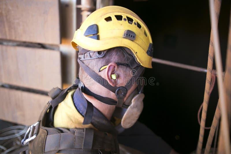 佩带耳塞噪声安全保护的矿工工作者,当工作在运转寿命植物机械附近时 免版税图库摄影