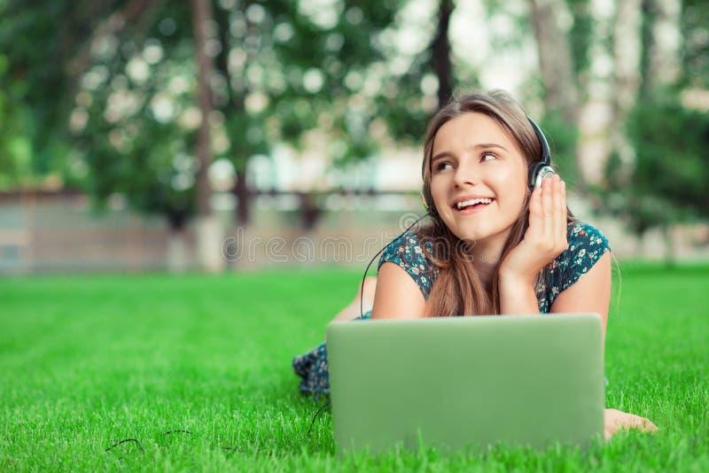 佩带耳机的妇女听到在膝上型计算机的喜爱mp3数字音乐外面在躺下的公园 库存图片