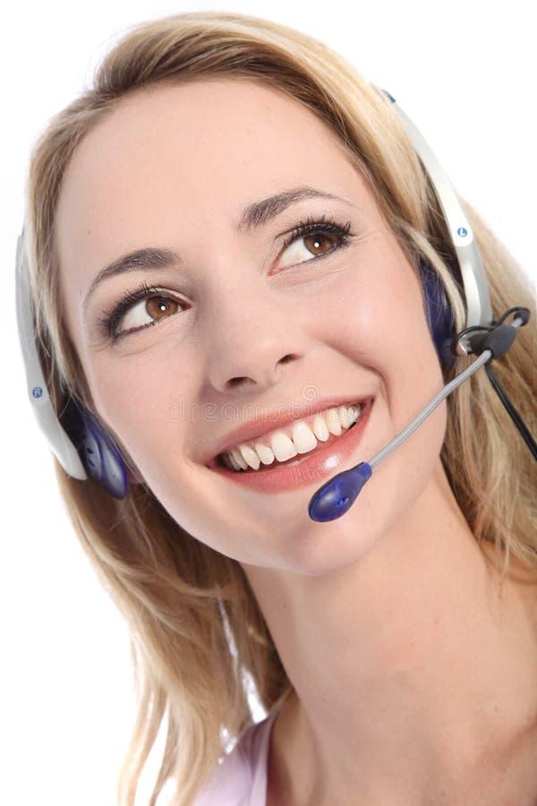 佩带耳机的微笑的招待员 免版税库存图片