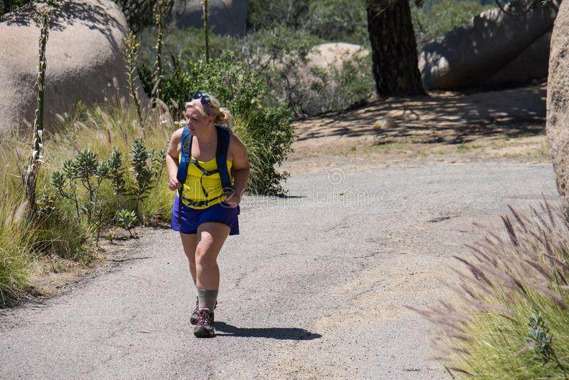 佩带背包和远足一条老火路的一个白肤金发的女性徒步旅行者起动步行在薯片岩石足迹在雷蒙娜附近, 库存照片