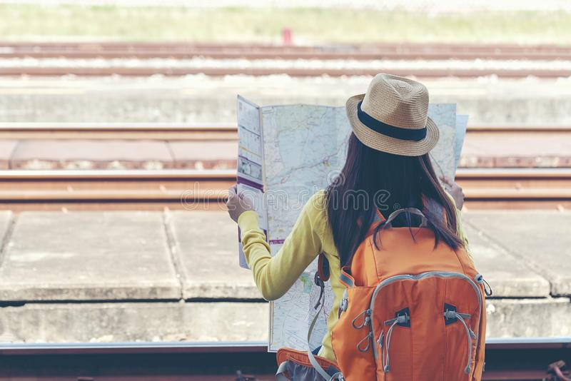 佩带背包藏品地图的旅客和旅游亚裔年轻女人,等待火车 库存照片