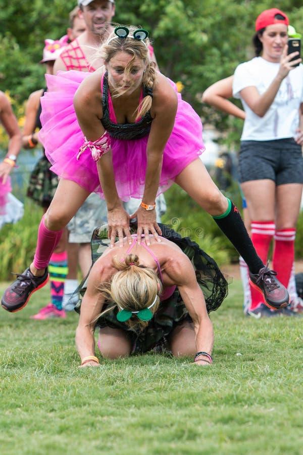 佩带芭蕾舞短裙戏剧飞跃青蛙的妇女在野外演习日事件 图库摄影