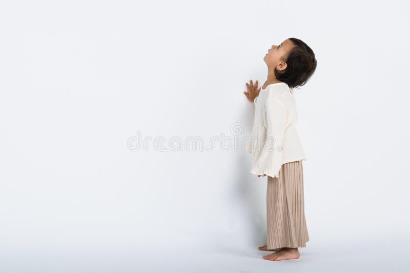 佩带花冠和看照相机和微笑与一个愉快的smileStudio充分的身体po的一个女孩的演播室画象 免版税库存照片