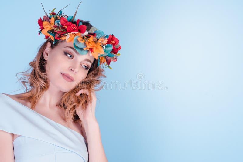佩带花卉头饰带冠状头饰冠的美丽的年轻女人隔绝了与色的花的浅兰的背景在头 免版税库存图片