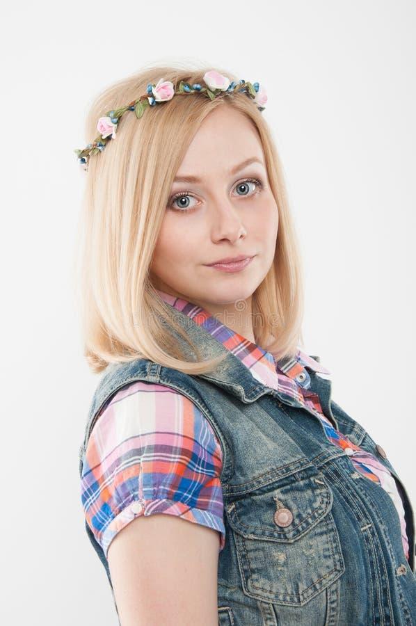 佩带花的年轻美丽的妇女在她的头缠绕 免版税库存图片