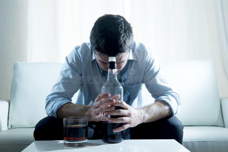 佩带蓝色宽松领带的醺酒的商人喝与在长沙发的威士忌酒瓶 免版税图库摄影