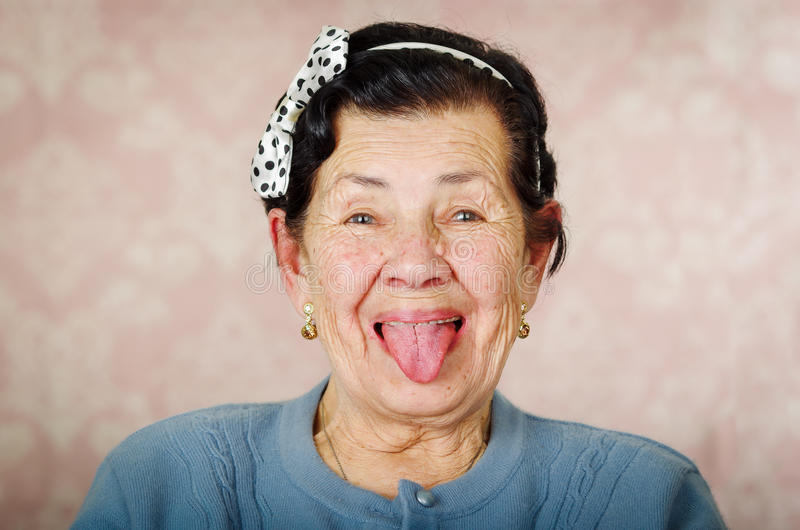 佩带蓝色毛线衣和圆点bowtie在头的更老的逗人喜爱的西班牙妇女显示她的舌头对照相机在前面 图库摄影