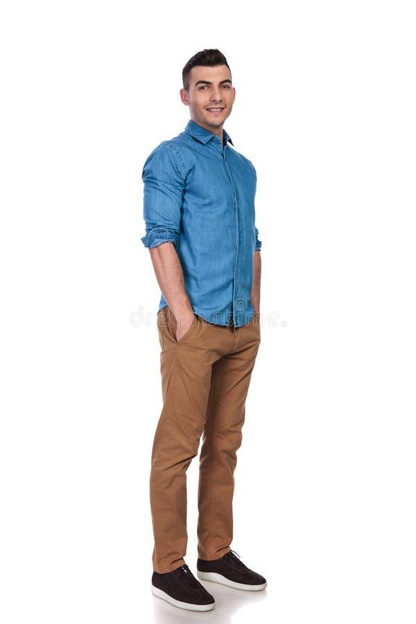 佩带蓝色衬衣立场用在口袋的手的帅哥 库存图片