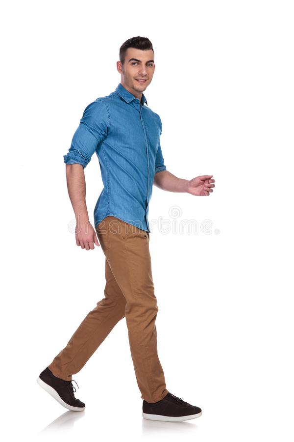 佩带蓝色衬衣走的英俊的偶然人侧视图  图库摄影