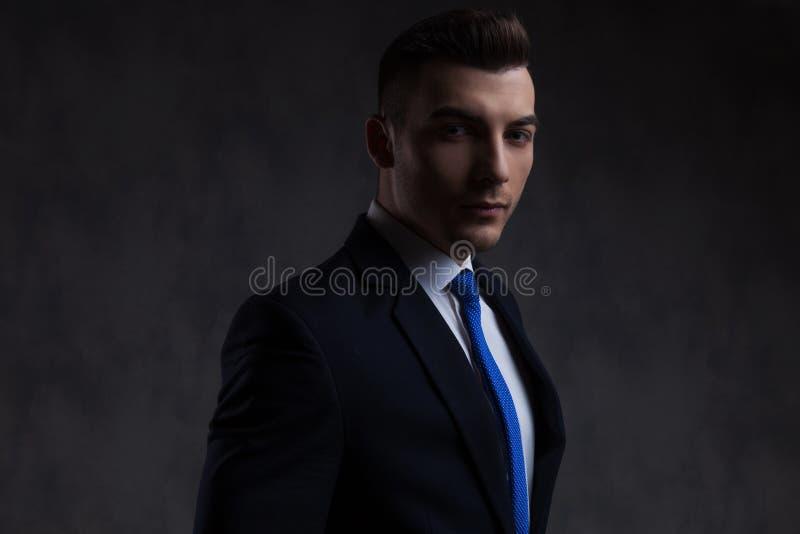 佩带蓝色领带身分的可爱的商人画象 免版税库存图片