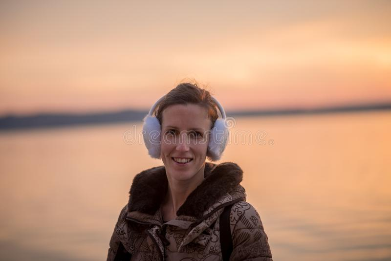 佩带蓬松耳朵笨拙的人的微笑的妇女在日落 库存照片