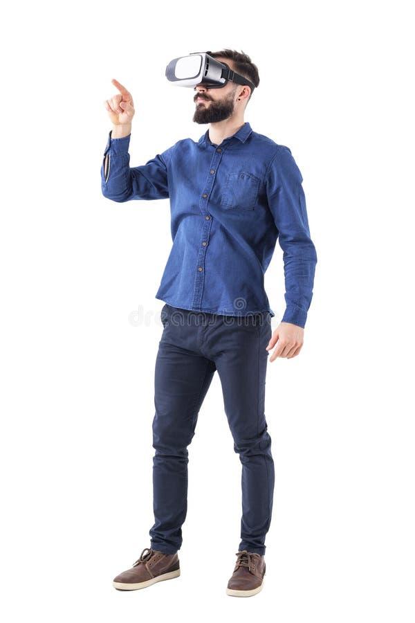 佩带虚拟现实的年轻有胡子的商人使用在被增添的现实触摸屏上的手指 库存照片