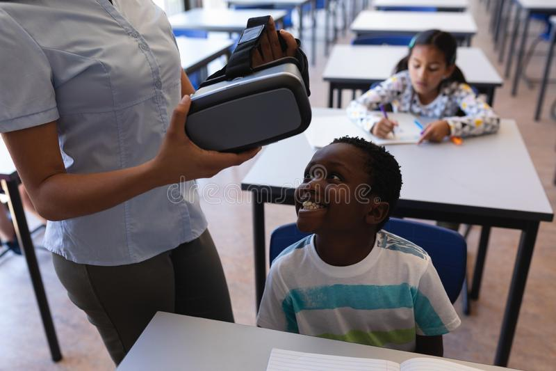 佩带虚拟现实耳机的女老师对男小学生在书桌在教室 免版税库存照片