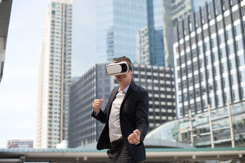 佩带虚拟现实耳机VR和战斗由拳打的白种人商人对空气 图库摄影