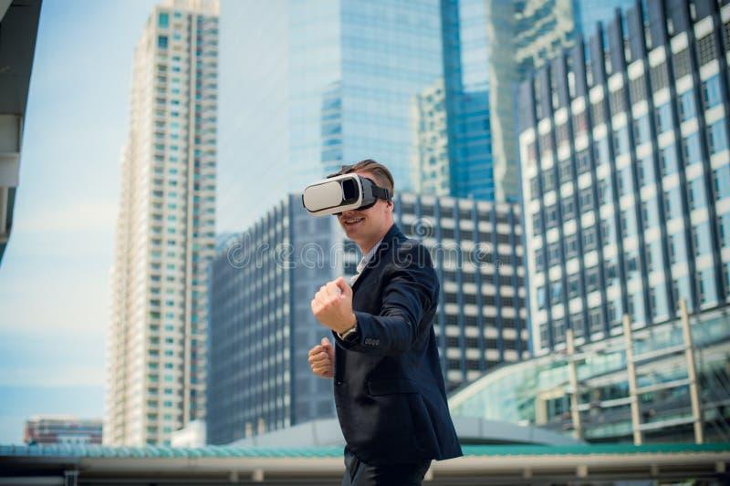 佩带虚拟现实耳机VR和战斗由拳打的白种人商人对空气 免版税库存图片