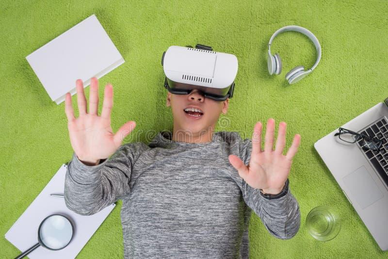 佩带虚拟现实风镜的亚裔人顶视图 人说谎 免版税库存图片