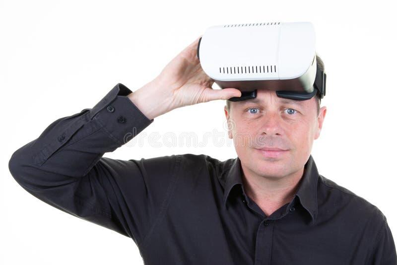 佩带虚拟现实风镜的年轻帅哥在黑VR概念的衬衣白色背景演播室 免版税库存照片